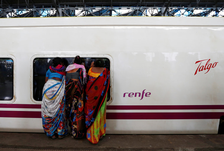 Image: People look inside the parked high speed Talgo train during its trial run at a railway station in Mumbai