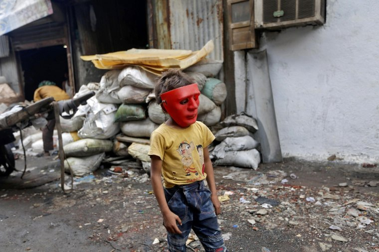 Image: A boy wearing a plastic mask walks in an industrial area in Mumbai