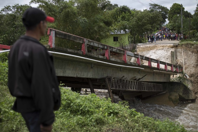 Residents stand before a collapsed bridge brought down by Hurricane Earl in the Arroyito neighborhood, in Melchor de Mencos, Guatemala, on the Peten border with Belize, Thursday, Aug. 4, 2016.
