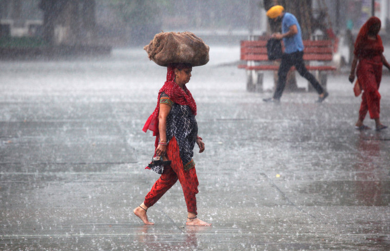 Image: A woman carries a sack outside a market during heavy rains in Chandigarh