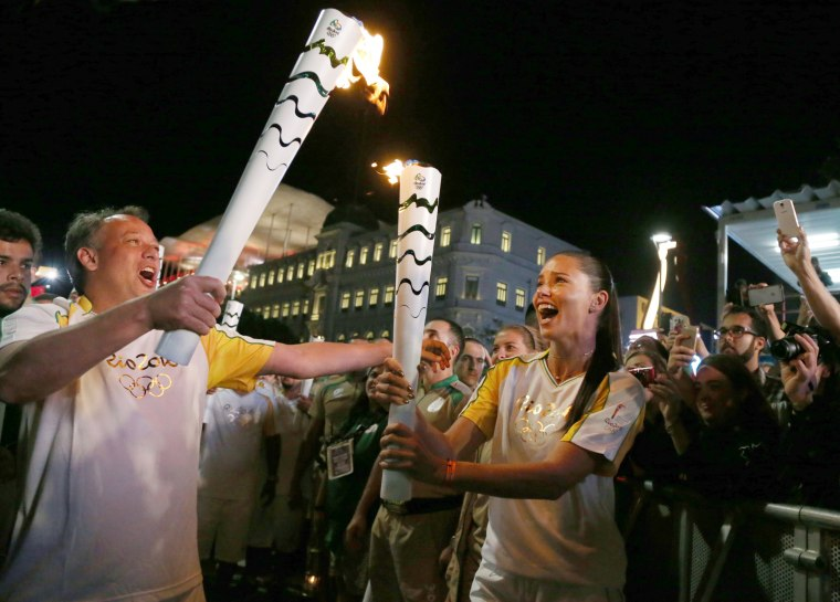 Image: Model Adriana Lima carries the Olympic torch with Rio de Janeiro's Secretary of Tourism Antonio Pedro in Maua Square in Rio de Janeiro