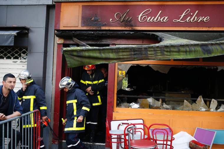 Image: Firefighters leave after inspecting the damaged Au Cuba Libre