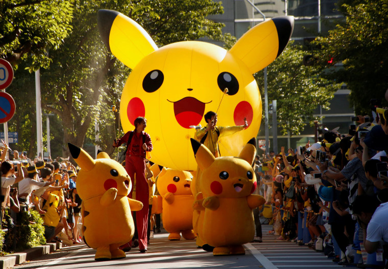 Image: Performers wearing Pokemon's character Pikachu take part in a parade in Yokohama