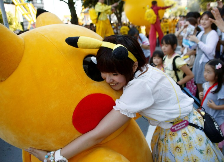 Image: A woman hugs a performer wearing Pokemon's character Pikachu during a parade in Yokohama