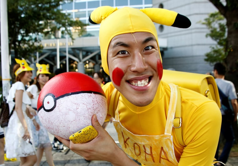 Image: A man wearing Pokemon's character Pikachu costume poses to a camera prior to a parade by performers wearing Pikachu costumes in Yokohama