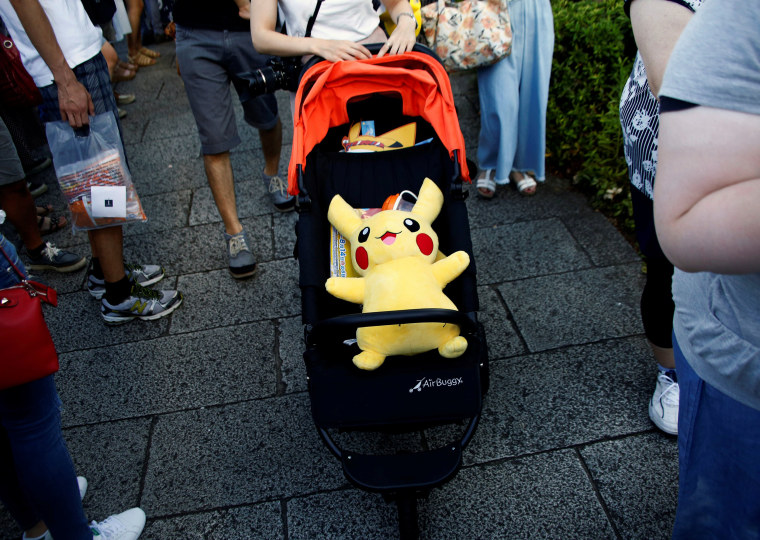 Image: A woman pushes a baby stroller with a Pokemon character Pikachu doll in Yokohama