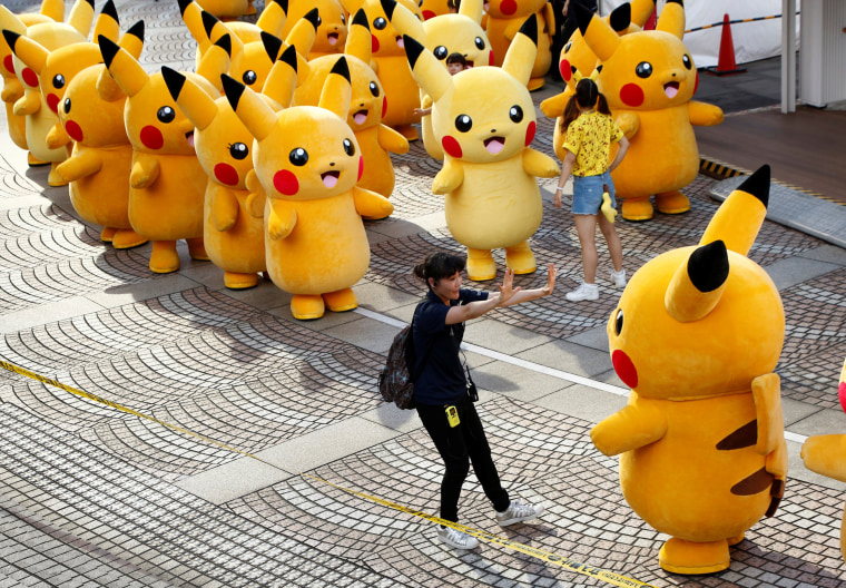 Image: A staff guides a performer wearing Pokemon's character Pikachu costume as they prepare for a parade in Yokohama