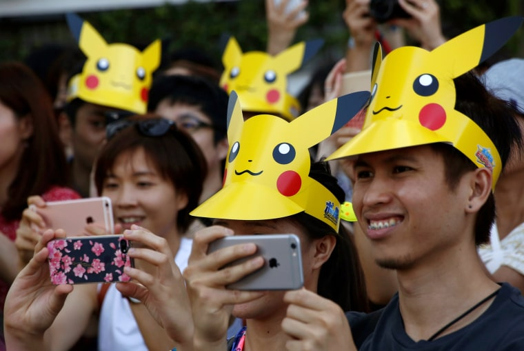 Image: People wearing 'Pikachu' hats take pictures of the parade by performers wearing Pokemon's character Pikachu costumes in Yokohama