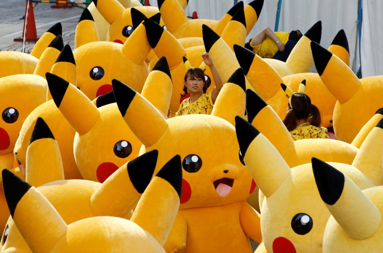 Image: A staff guides performers wearing Pokemon's character Pikachu costumes as they prepare for a parade in Yokohama