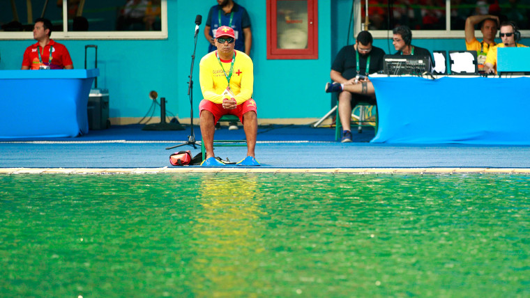 A lifeguard sits by the edge of the diving pool that has turned green.