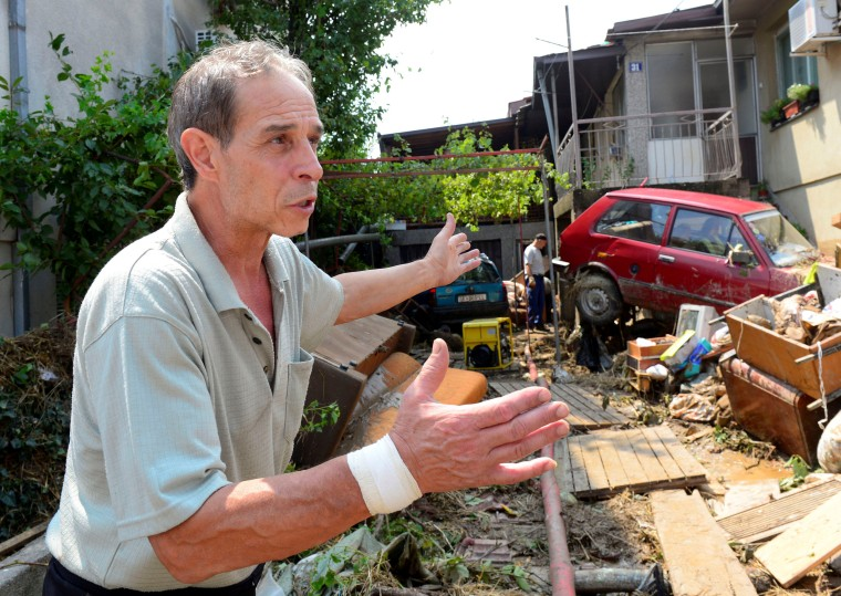Image: A man shows the damage after heavy floods in Cento