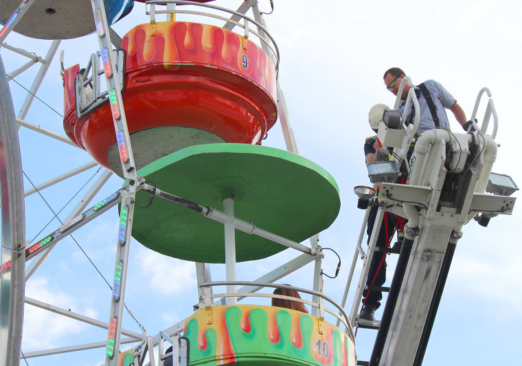 Image: Members of the Greeneville Fire Department help people off the ferris wheel at the Greene County Fair