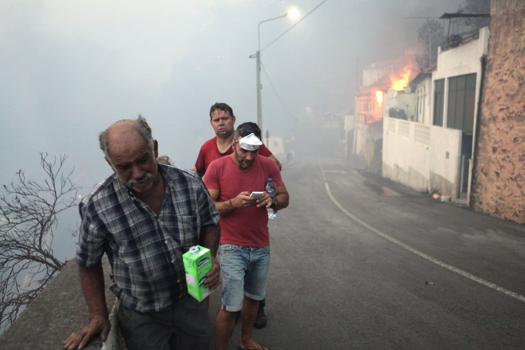 Image: People on the streets of Bom Sucesso, near to a fire during the wildfires at Funchal, Madeira island