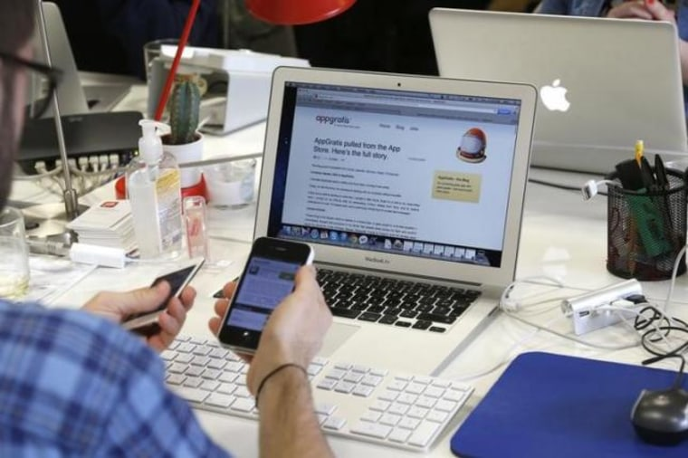 An employee uses his Iphone as he works on a computer screen displaying the AppGratis blog in the offices of AppGratis company in Paris