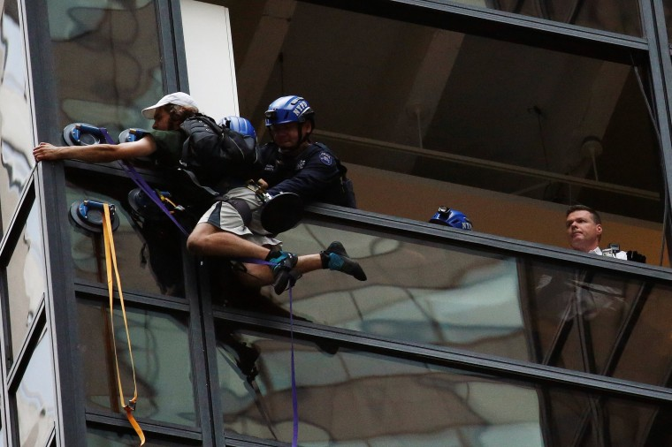 Image: Officers from the NYPD embrace a man to stop him from climbing the outside of Trump Tower in New York
