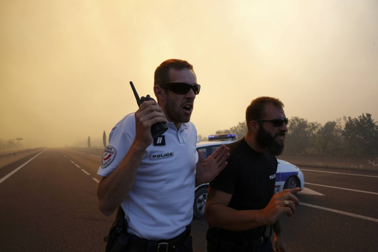 Image: French police stand at a roadblock as smoke fills the sky and blocks the sun as fires burn north of Marseille