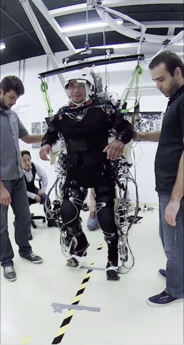 Patient in a training session using harnesses and assistance to learn to regain control of their legs.