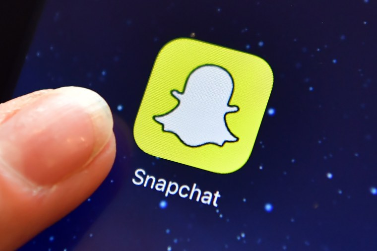 A finger is posed next to the Snapchat app logo on an iPad on August 3, 2016 in London, England.