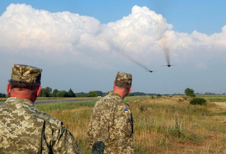 Image: Ukrainian servicemen watch Sukhoi Su-24 front-line bombers fly during military aviation drills as Russia accuses Ukraine in incursion into annexed Crimea, in Rivne region