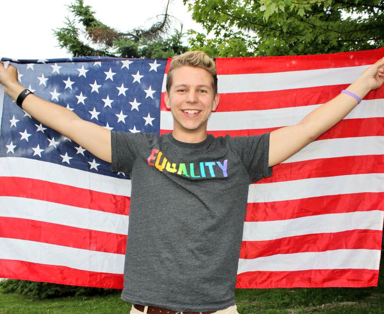 Cole Ledford holds up flag at an LGBTQ equality event in NYC (2016).