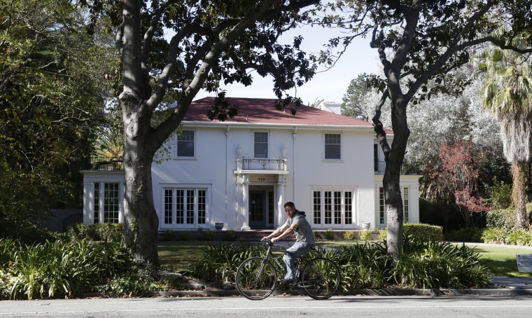 A man cycles past a large home on Thursday, Oct. 23, 2014, in Palo Alto, Calif. The Silicon Valley city of Palo Alto has two different economic dynamics, on the east side, lies a rougher neighborhood of working class residents and new immigrants. On the west side, is a more affluent population centered around world renowned Stanford University.