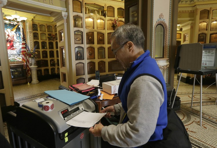Image: Jeff Young enters a ballot into a voting machine in San Francisco