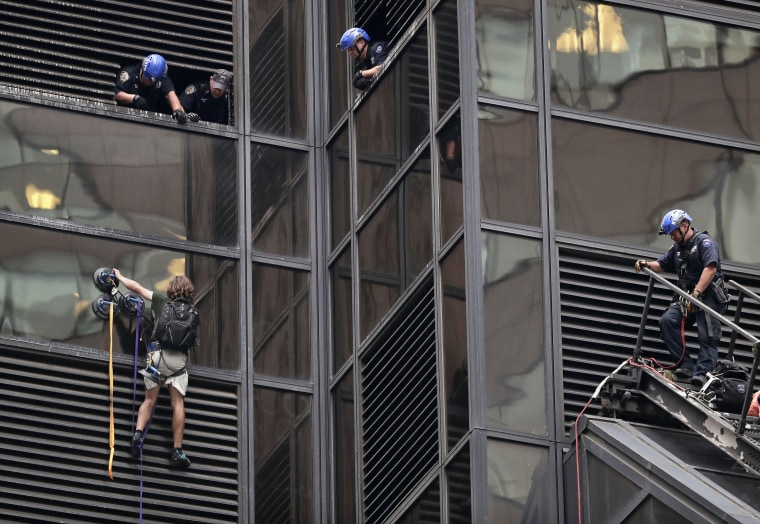 Image: A man scales the all-glass facade of Trump Tower