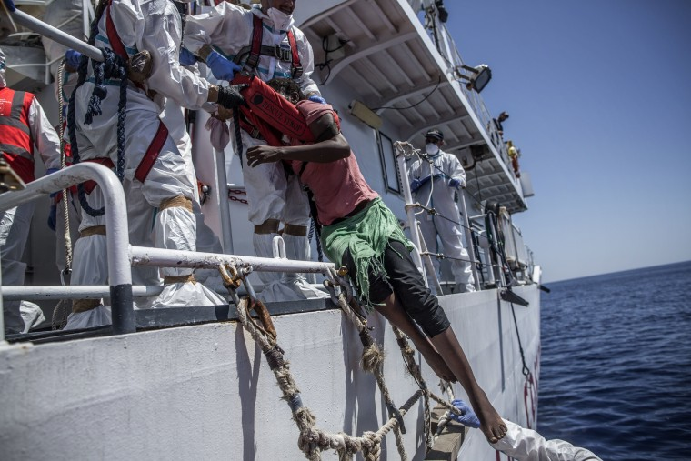 Image: A migrant is pulled up into a vessel by members of the Italian Coast Guard in the central Mediterranean Sea