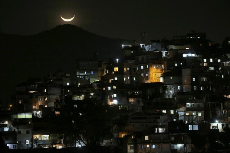 Image: The moon is seen over a slum near Copacabana Beach in Rio de Janeiro, Brazil