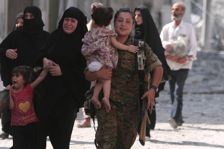 Image: A Syria Democratic Forces (SDF) fighter helps civilians who were evacuated from an ISIS-contolled part of Manbij in northern Syria.