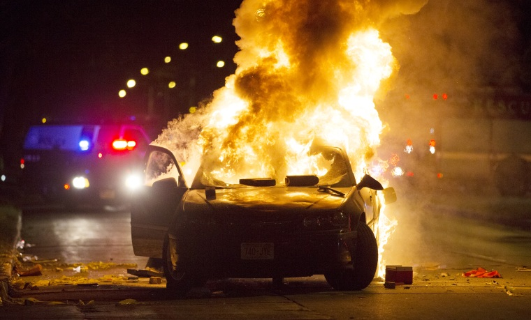 A car burns as a crowd of more than 100 people gathers following the fatal shooting of a man in Milwaukee, Saturday, Aug. 13, 2016.