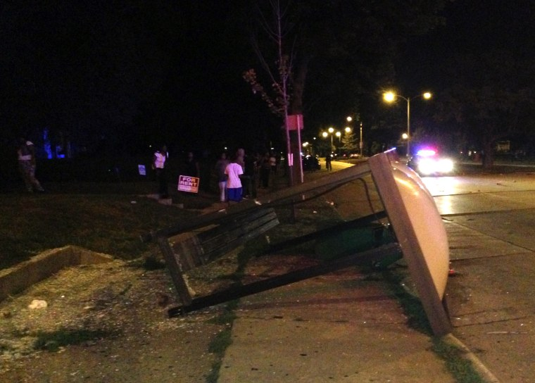 An overturned bus shelter lies on the ground after dozens of people protested following the fatal shooting of a man in Milwaukee, Saturday, Aug. 13, 2016.
