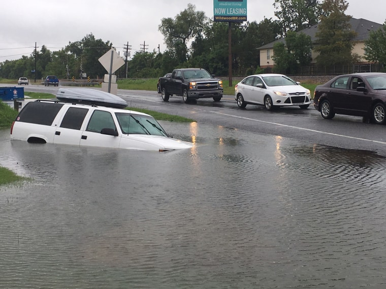 Image: Vehicles pass a submerged car in a ditch