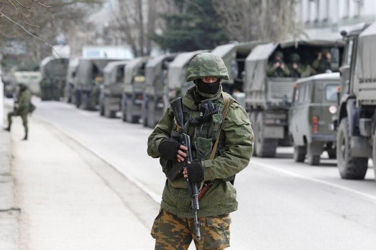 Image: Armed servicemen wait in Russian army vehicles outside a Ukranian border guard post in the Crimean town of Balaclava