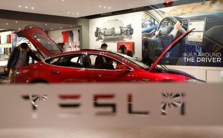 A man looks around Tesla Motors' Model S P85 at its showroom in Beijing