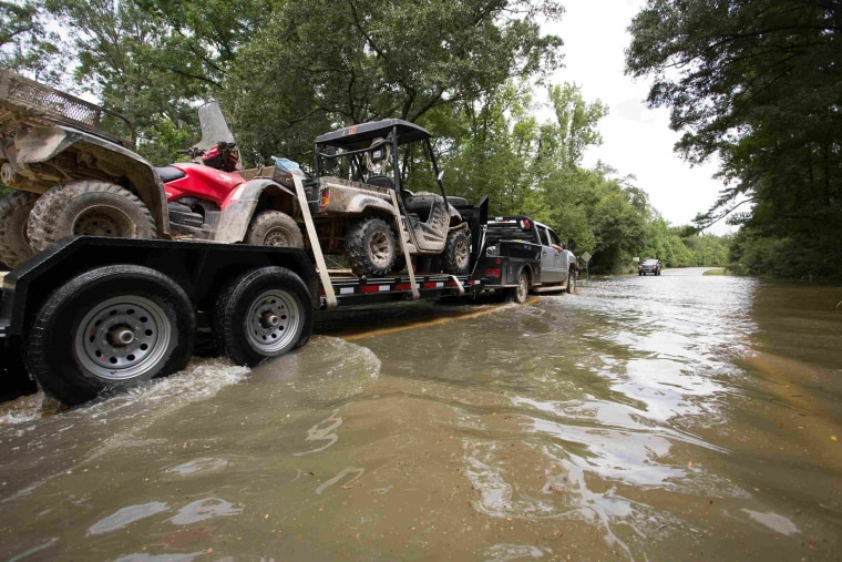 Image: A truck pulling ATVs drives through the remaining floodwaters on Liberty Road in Greenwell Springs