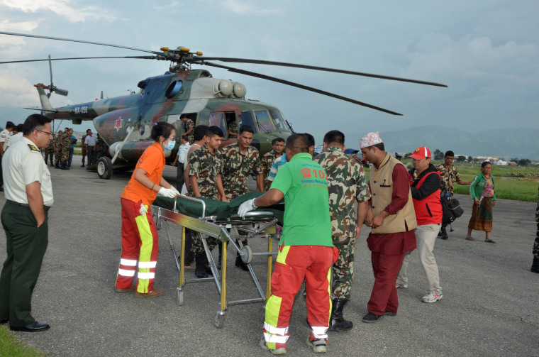 Image: Nepalese army personnel assist a victim of a bus accident
