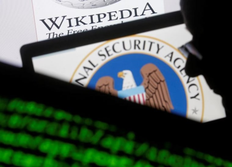 A man is seen near cyber code and the U.S. National Security Agency logo in this photo illustration taken in Sarajevo