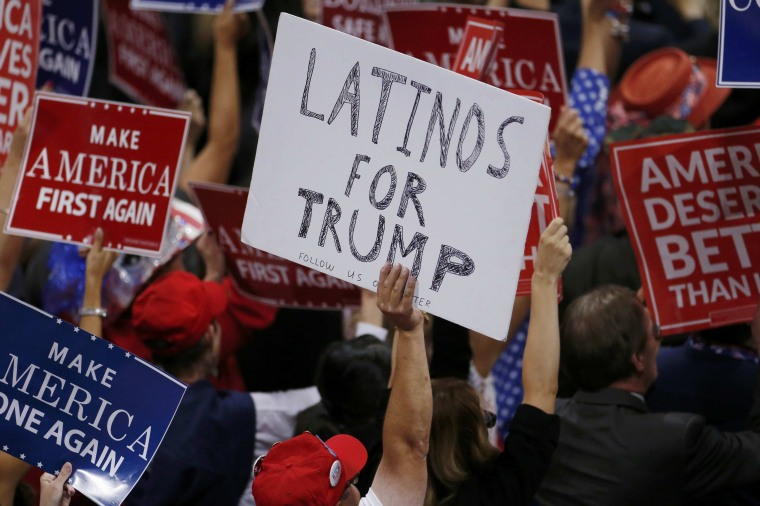 Image: A person holds a sign reading Latinos for Trump on the third day of the Republican National Convention in Cleveland, Ohio