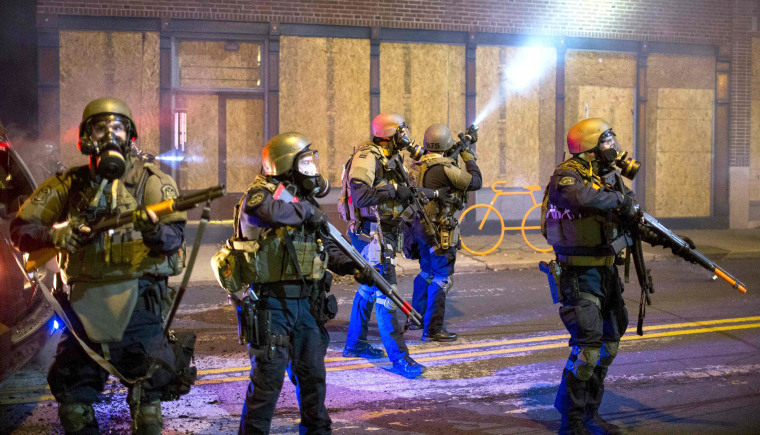 Image: Police officers react to violent protesters during a second night of protests in Ferguson, Missouri