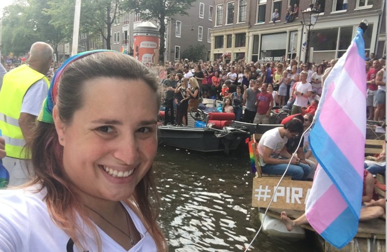 Trans activist Hannah Simpson, waving the transgender pride flag, takes a selfie from aboard the World Religion Boat during Amsterdam's EuroPride 2016 Canal Parade.