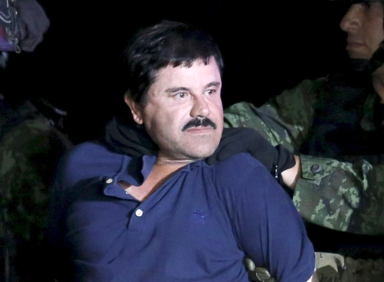 """Image: Recaptured drug lord Joaquin """"El Chapo"""" Guzman is escorted by soldiers during a presentation in Mexico City"""