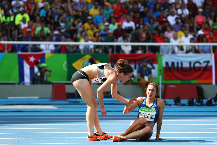 Image: Abbey D'Agostino of the United States (R) is assisted by Nikki Hamblin of New Zealand