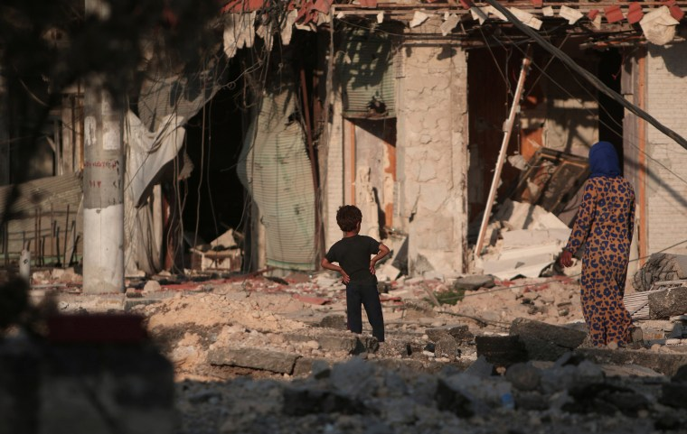 Image: A woman walks with a boy on the rubble of damaged shops and buildings in Manbij, Aleppo Governorate