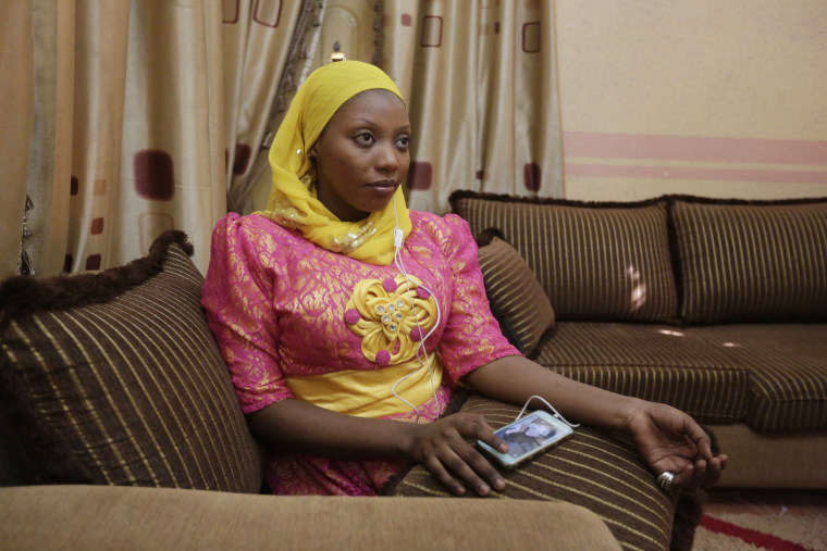 In this photo taken Tuesday April, 5. 2016, Khadija Gudaji, a Physics student of Northwest University listen to daily radio talk show on her mobile phone in Kano, Nigeria. In the local market stalls are signs of a feminist revolution with piles of poorly printed books by women, as part of a flourishing literary movement centered in the ancient city of Kano, that advocate against conservative Muslim traditions such as child marriage and quick divorces.  dozens of young women are rebelling through romance novels, many hand-written in the Hausa language, and the romances now run into thousands of titles.