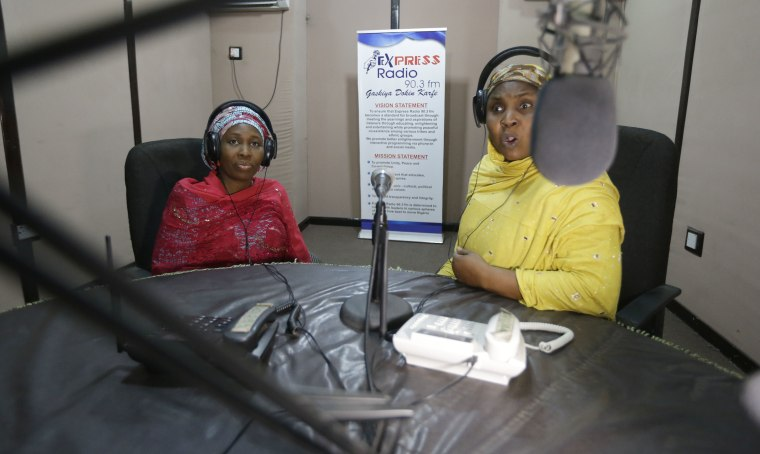 In this photo taken Tuesday April, 5. 2016 author Hadiza Nuhu Gudaji, left, during a radio talk show on her novels in Kano, Nigeria. Dozens of young women are rebelling through romance novels, many hand-written in the Hausa language, and the romances now run into thousands of titles.