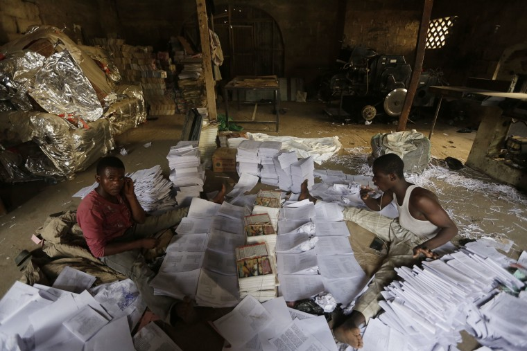 In this photo taken Sunday April, 3. 2016, young men sort out newly printed books in Kano, Nigeria.