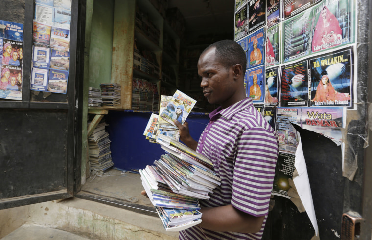In this photo taken Monday April, 4. 2016, a Book hawker, Adamu Saidu, displays books he purchased at Kurmi Market to be sold in villages inaccessible by car in Kano, Nigeria. In the local market stalls are signs of a feminist revolution with piles of poorly printed books by women, as part of a flourishing literary movement centered in the ancient city of Kano, that advocate against conservative Muslim traditions such as child marriage and quick divorces.