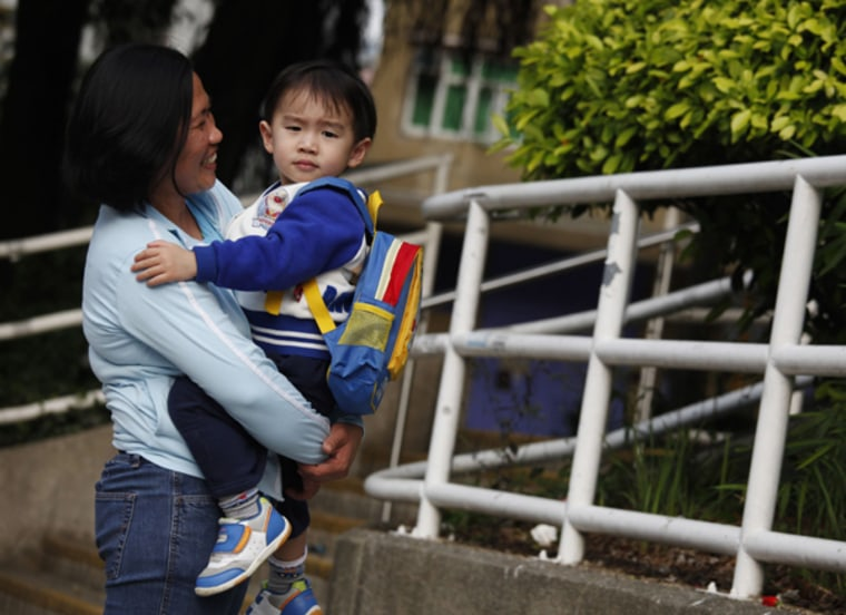 Susan Famadula holds Ka-hei, 3, the child of her employers whom she is hired to look after, in Hong Kong