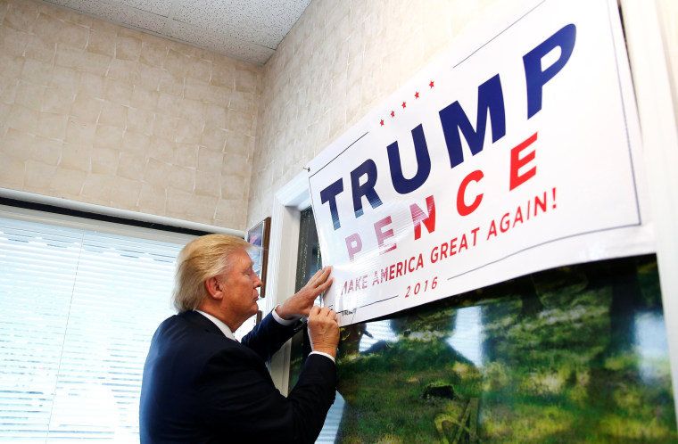Image: Republican U.S. presidential nominee Donald Trump signs a poster during a visit to Allegra Print and Imaging in Fayetteville